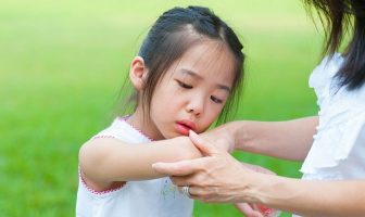 mother checking wound to her daughter at outdoor park