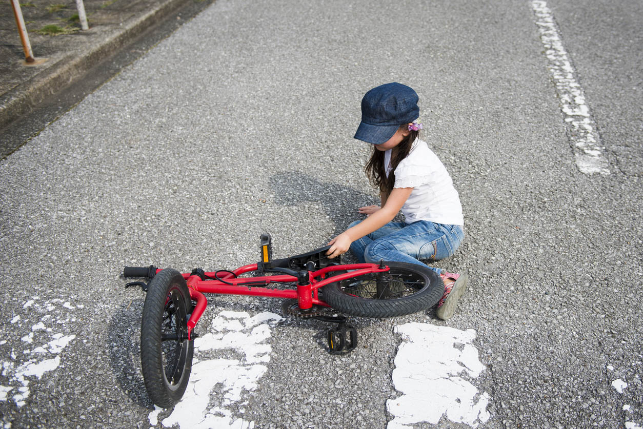 Little girl who has fallen from bicycle